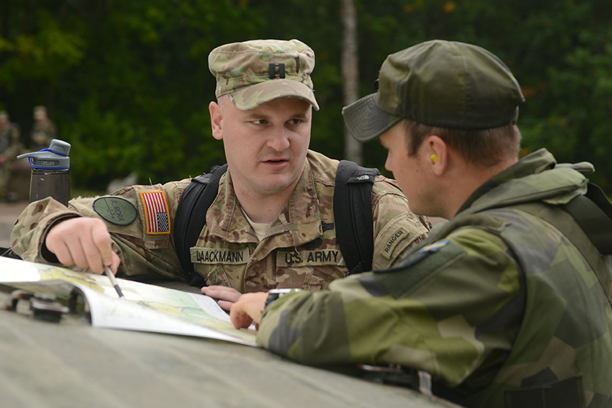 Moments before moving out Capt. Jason Laackmann, Charlie Company Commander, briefs his Swedish counterpart on intended movement techniques during training Sept. 12, 2017 near Skovda, Sweden. (Minnesota National Guard photo by Staff Sgt. Anthony Housey)