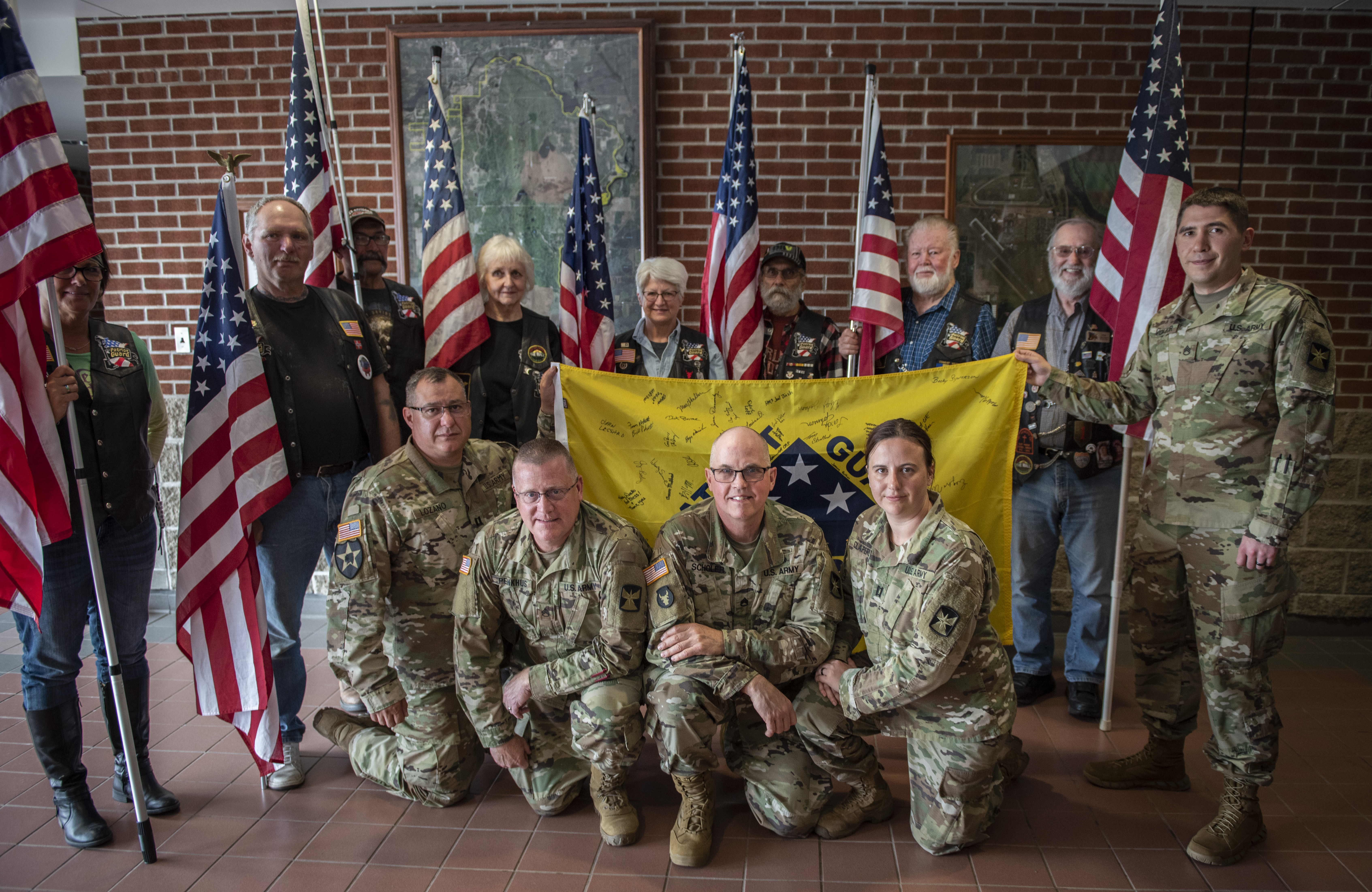 The Minnesota Patriot Guard, whose volunteers are at every mobilization event, say farewell and present a flag to the 1904th Acquisition Team on June 23 at Camp Ripley Training Center. The five-person contracting team is headed to Kuwait to plan and coordinate contract functions in the theater, and act as contract officer representatives to ensure contracts are properly administered.